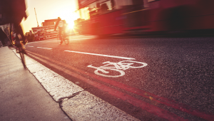 A cyclist follows a cycle lane in London, as a bus passes by