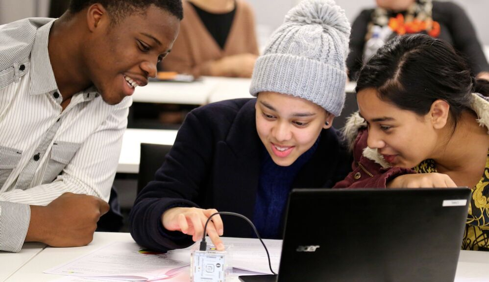 A UCL Engineering Engagement Team volunteer and young female pupils learn whilst having fun at the 'Change the World' Engineering Masterclass Series for East London schools